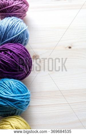Multicolored Woolen Balls On Wooden Background. Vertical Format With Left Border. Knitting As Hobby.