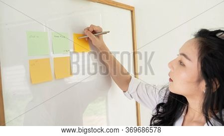 A Woman Using Sticky Postit And Analysis Data Report During Writing Make Note Some Data On Notepad,
