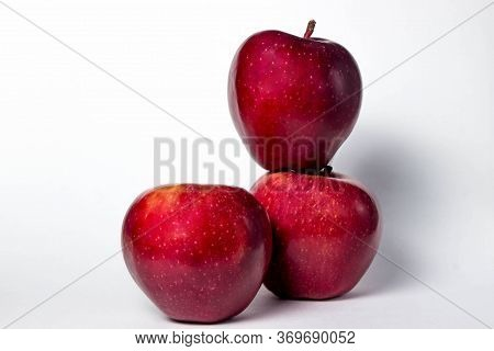 Three Red Apples On A White Background. One Apple Lies On Another Apple. The Third Apple Lies Ahead