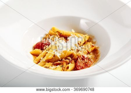 Penne in tomato sauce. Served traditional Italian cuisine. Pasta with grated parmesan cheese in plate. Italy culinary. Restaurant food portion, delicious supper, main course close up