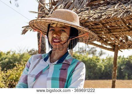 Taungoo, Myanmar - January 26, 2020: Burmese Woman In Traditional Thanaka Makeup And Straw Hat