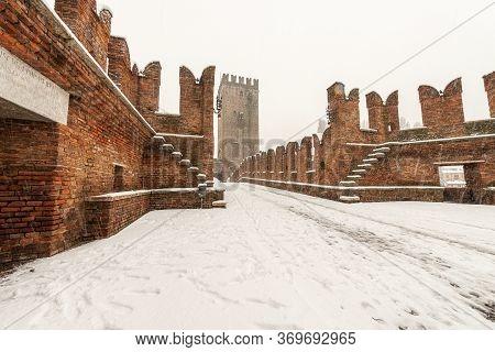 Ancient Scaligero Bridge Of Castelvecchio In Winter While It Snows. Old Castle In Verona, Unesco Wor