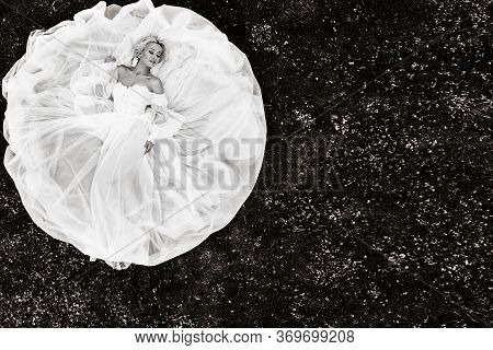 Portrait Of A Beautiful Bride Lying On The Ground In A White Wedding Dress.photo Of An Elegant Bride