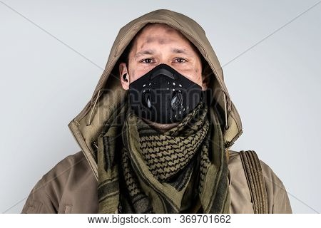 Young Handsome Man With Ax Wearing Black Protactive Face Mask And Jacket With Hood On Gray Backgroun