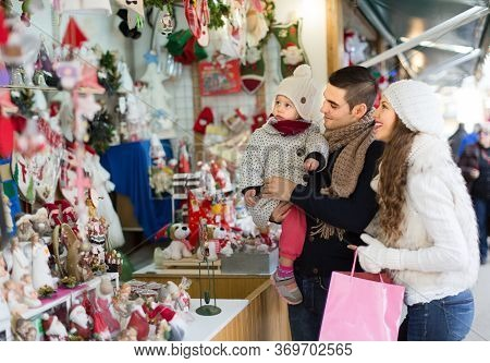 Smiling Parents With Child At Counter Of X-mas Market Together