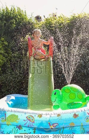 Child Having Fun Playing In Water In A Garden Paddling Pool The Boy Is Happy And Smiling