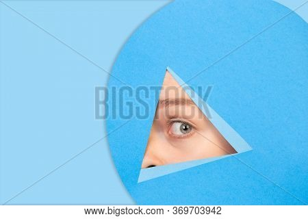 Close Up Female Eye Peeks, Looks Throught Triangle In Blue Background. Trendy Geometrical Style, Cop