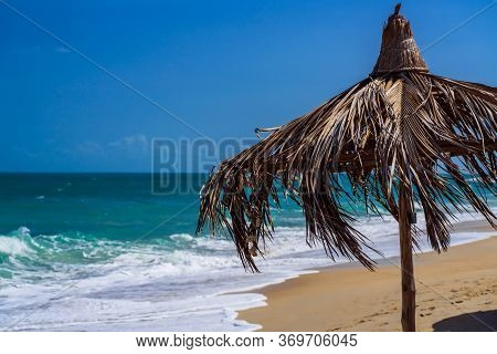 Hand-made Straw Sunshade On The Beach On Background Of The Ocean. Sun Umbrella On The Background Of