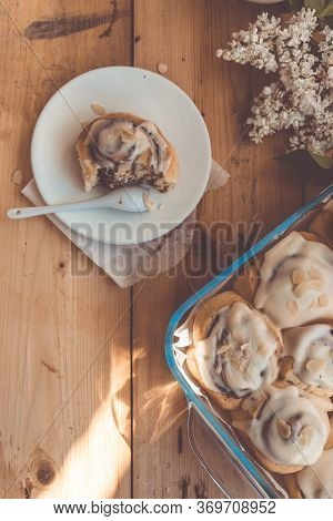 Freshly Baked Cinnabon Buns With Butter Cream In A Glass Dish And A Slice Of Bun On A Plate On A Woo