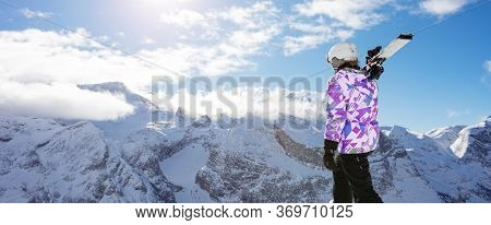 Back View Of The Girl Skier On Top Of The Mountain Stand, Hold Ski On The Shoulder Over Peaks And Cl