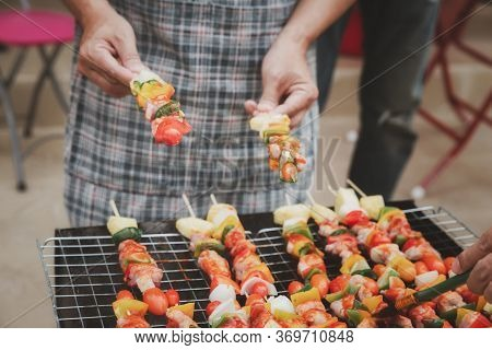 A Man Grilling Pork And Barbecue In Dinner Party. Food, People And Family Time Concept.
