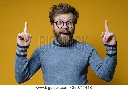 Great Idea. Shaggy, Bearded Man With Glasses And A Blue Sweater Raises Index Fingers Up And Looks Jo