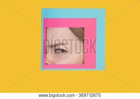 Doubt. Face Of Emotional Caucasian Woman Peeks Throught Square In Yellow Background. Trendy Geometri