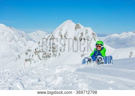 Portrait Of A Little Snowboarder Sit In Snow With Snowboard Over Mountain In Bright Blue And Green S