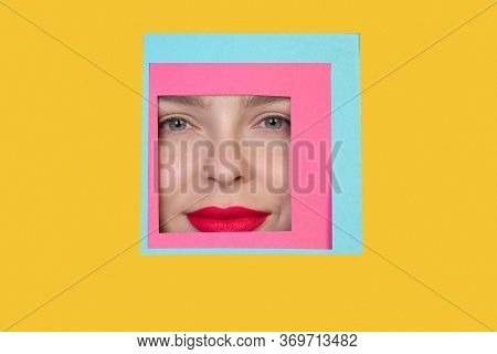Serious. Face Of Emotional Caucasian Woman Peeks Throught Square In Yellow Background. Trendy Geomet