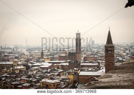 Aerial View Of Verona Downtown In Winter With Snow. Church Of Santa Anastasia And Medieval Tower Of