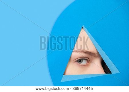 Serious. Face Of Emotional Caucasian Woman Peeks Throught Triangle In Blue Background. Trendy Geomet