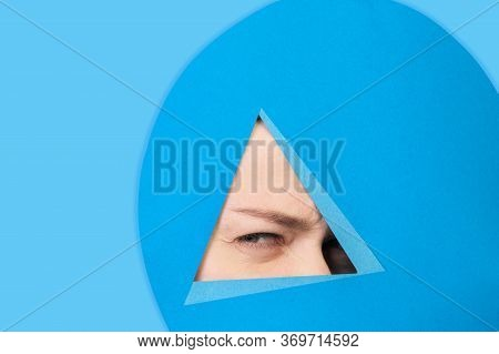 Angry. Face Of Emotional Caucasian Woman Peeks Throught Triangle In Blue Background. Trendy Geometri