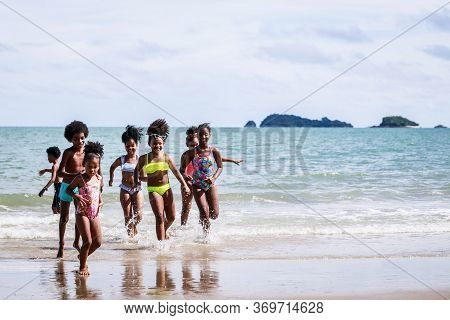 African American, Kids Group In Swimwear Enjoying Running To Play The Waves On Beach. Ethnically Div