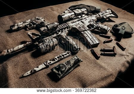 Photo Of A Camouflaged Military Ar-15 Rifle With Scope Laying With Knife, Gun And Tactical Gloves Si
