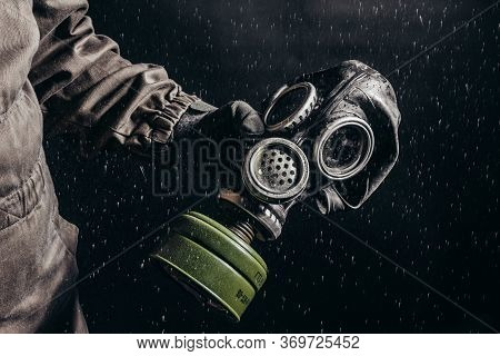 Photo Of A Stalker  Holding Soviet Gas Mask During Rain On Black Background.