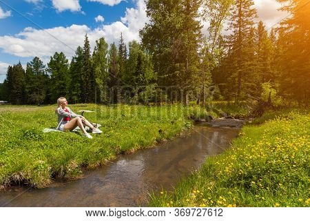 A Blonde Girl Sits In A Clearing Against A Forest And Blue Sky Next To A Stream, Her Eyes Closing In