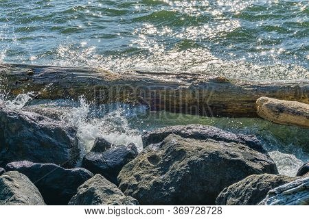 Waves Hit A Log And Rocks In The Pacific Northwest.