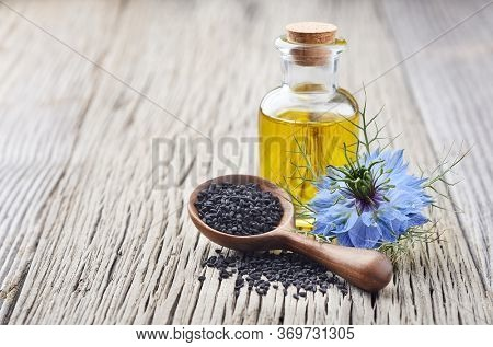 Black cumin oil with flower nigella sativa on wooden background