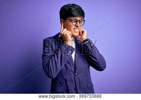 Young handsome business man wearing jacket and glasses over isolated purple background covering ears with fingers with annoyed expression for the noise of loud music. Deaf concept.