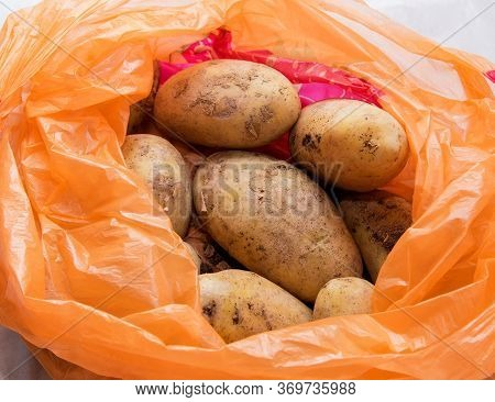 A Pile Of Unwashed Potatoes Lies In A Bright Bag