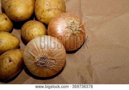 Unwashed Potatoes And Onions Lie On A Paper Bag