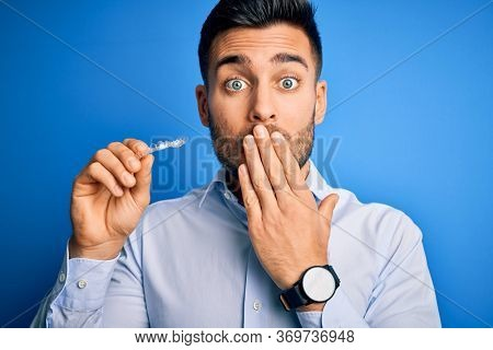 Young handsome man holding dental aligner tooth correction over blue background cover mouth with hand shocked with shame for mistake, expression of fear, scared in silence, secret concept