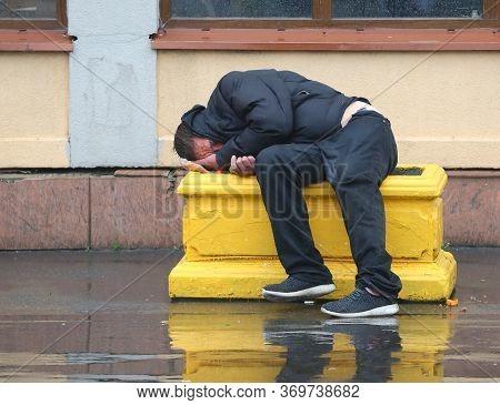 A Drunken Tramp Sleeps On A Yellow Concrete Flowerbed Against The Wall, Prospect Bolshevikov, Saint