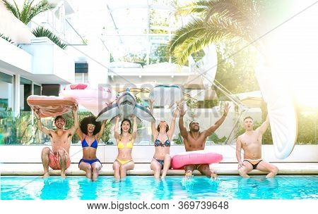 Front View Of Friends Sitting At Pool Party With Lilo Airbed And Swim Wear - Summer Lifestyle Concep