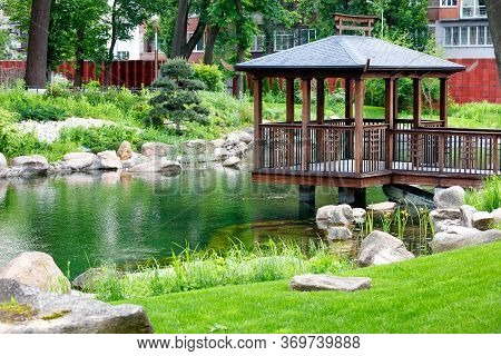 Wooden Openwork Arbor On Stilts Over The Water Of A Forest Lake, Surrounded By A Beautiful Park With