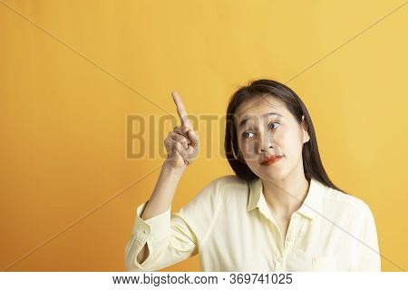 Beautiful Smiling Asian Woman Show Pointing  Hand To Empty Space Aside Studio Shot On Yellow Backgro