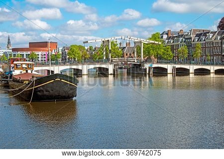 City scenic from Amsterdam at the river Amstel in the Netherlands with the Tiny Bridge