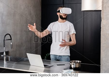 Selective Focus Of Man Using Vr Headset Near Gadgets And Medical Mask On Kitchen Worktop