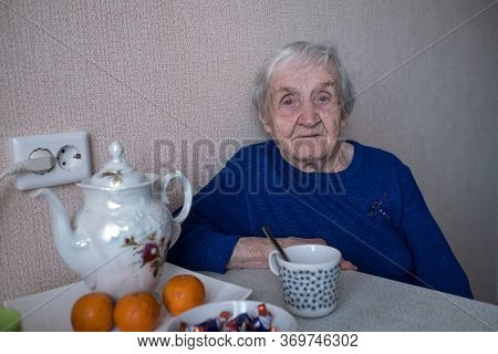 Elderly old russian woman in his house sad looks.