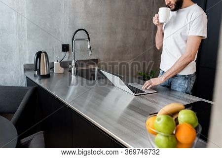 Cropped View Of Freelancer Holding Cup And Using Laptop On Kitchen Worktop