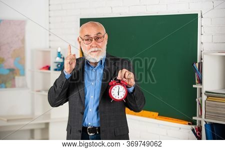 Time Is Our Future. Discipline And Punctuality. Senior Teacher Hold Alarm Clock. Time Management. Be