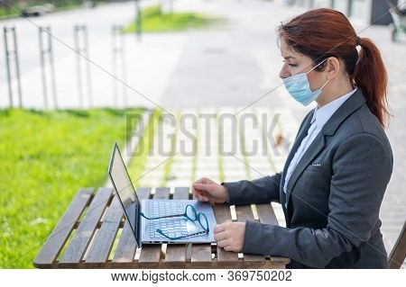 Serious Girl In Suit Works Remotely On A Laptop Outdoors. Business Woman Takes Off A Medical Mask Wh