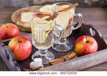 Warm Soothing Tea Made From Apples And Cinnamon In Glasses And Ingredients For Cooking On A Wooden T