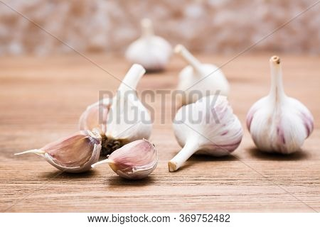 Garlic Bulbs Whole And Lobed On A Wooden Table. Alternative Medicine And Folk Remedies