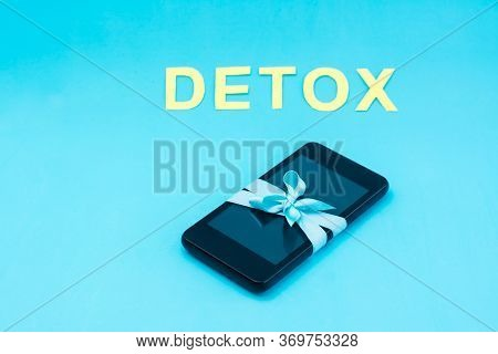 Digital Detox Concept. The Smartphone Is Tied With A Blue Ribbon And The Word Detox On A Blue Backgr