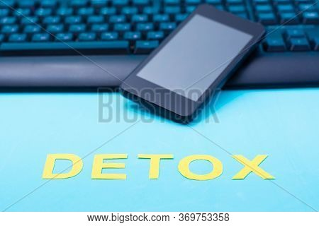 Digital Detox Concept. Word Detox On A Smartphone And Keyboard Background. Gadget Addiction