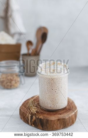 Close-up Of Jar With Natural Homemade Sourdough Levain Starter For Homemade Bakery