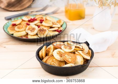 Trend Breakfast. Dutch Mini Pancakes In A Pan And On A Plate With Red Currants On A Wooden Table.