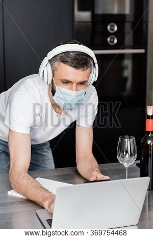 Freelancer In Medical Mask And Headphones Using Laptop Near Glass Of Wine On Worktop In Kitchen