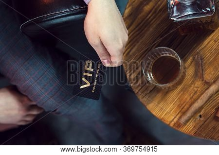 Man Holds Vip Member Card In His Hand. View From The Top On The Gentleman's Hand That Holds Exclusiv